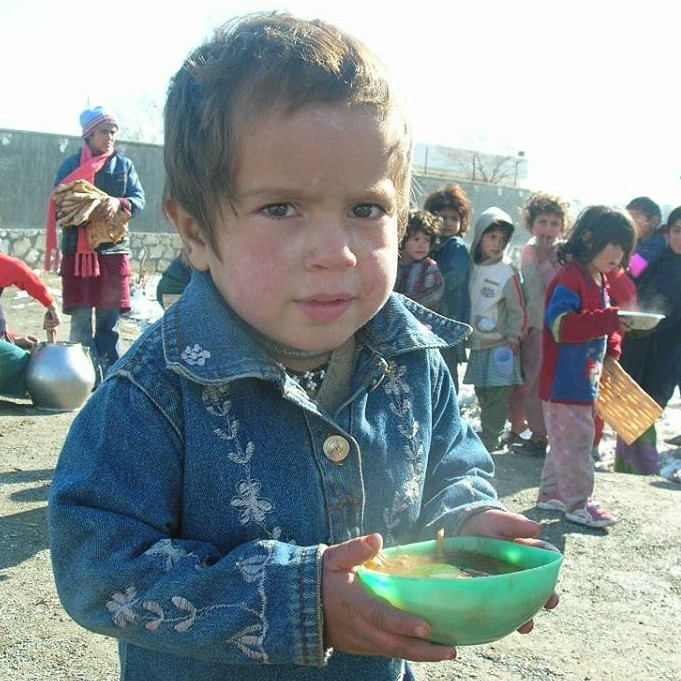 A child in Afghanistan receives a bowl of soup